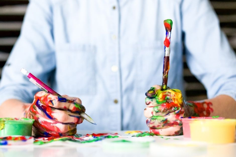 An image of an individual holding a pencil and paintbrush. The individuals forearm is covered in multicoloured paint splatters.