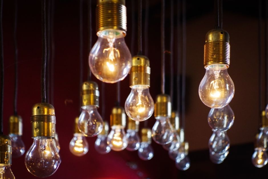 An image of hanging lightbulbs at varying lengths, some lightbulbs are lit whilst others are not.