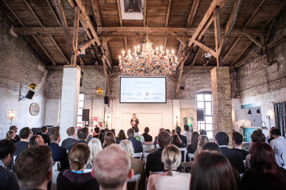 Event Saal mit Bühne, Franziska Kolbe hält Vortrag vor vielen Teilnehmern