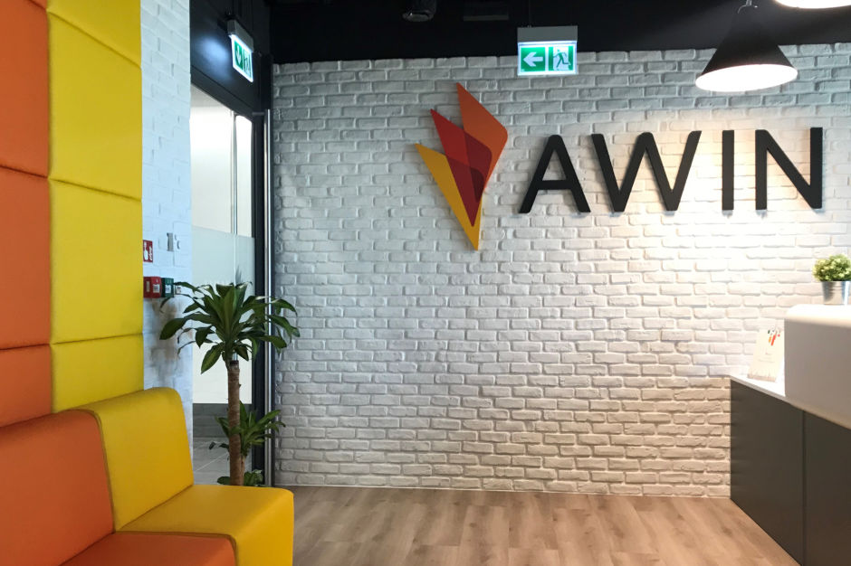 office wall made of white bricks with awin logo