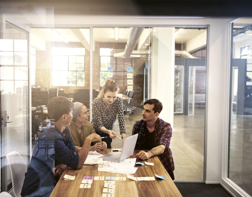 Vier Mensch stehen vor Laptop im Meetingraum