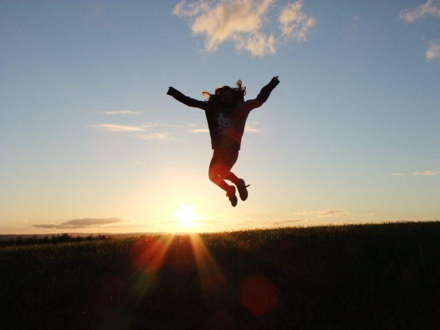 Frau macht bei Sonnenuntergang einen Luftsprung