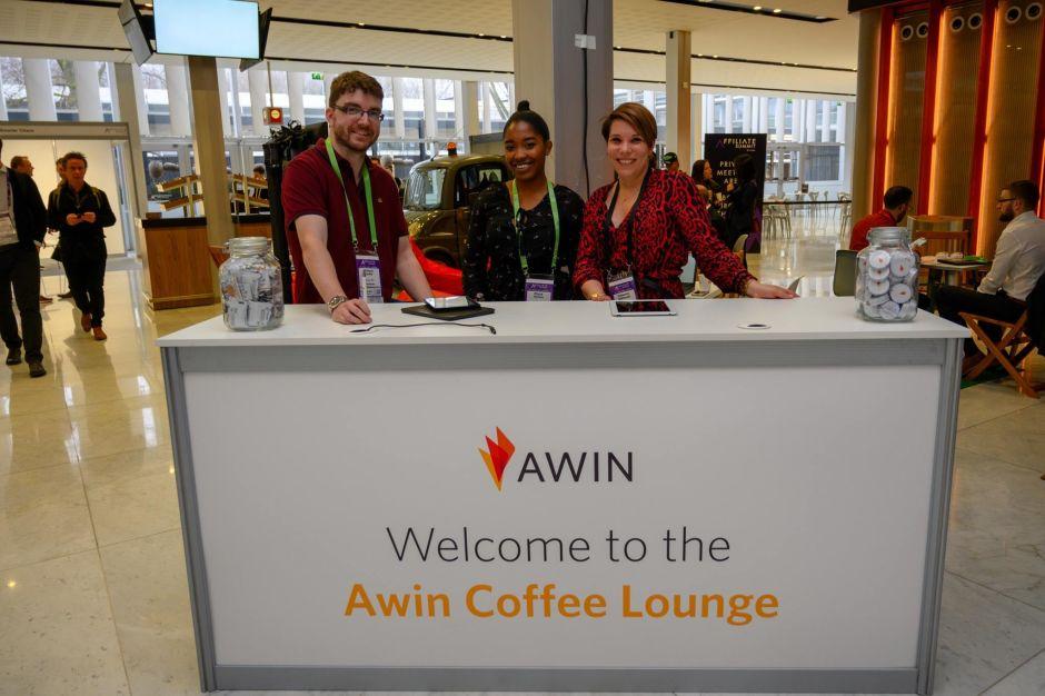 Drei Menschen hinter einem Counter mit Awin Logo