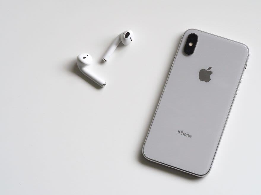 silbernes iPhone und Airpods auf weißer Unterlage