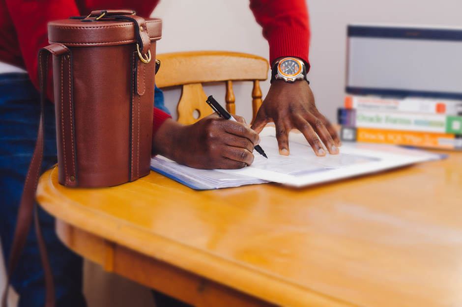 Man with watch on wrist signing contract on wooden table with leather bag and books