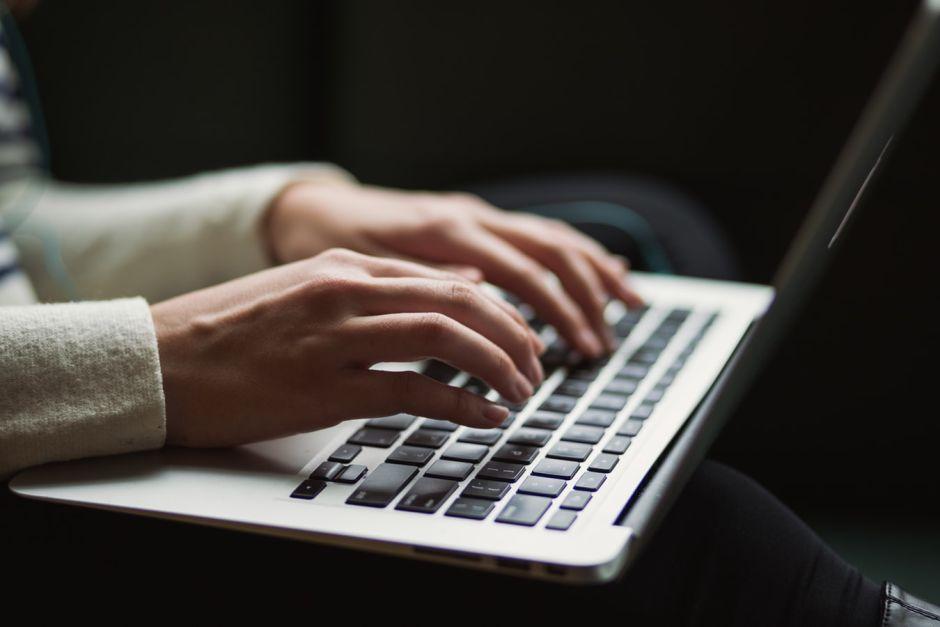 zwei Hände an einem Laptop