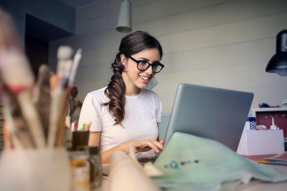 Frau mit Brille sitzt am Laptop und lächelt