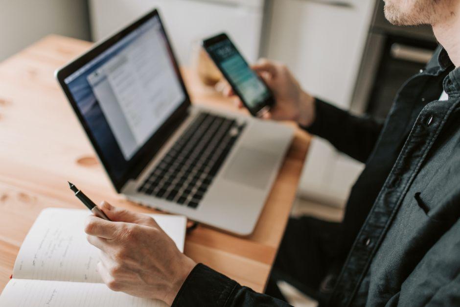 Person hält ein Handy in der einen Handy und sitzt am Laptop