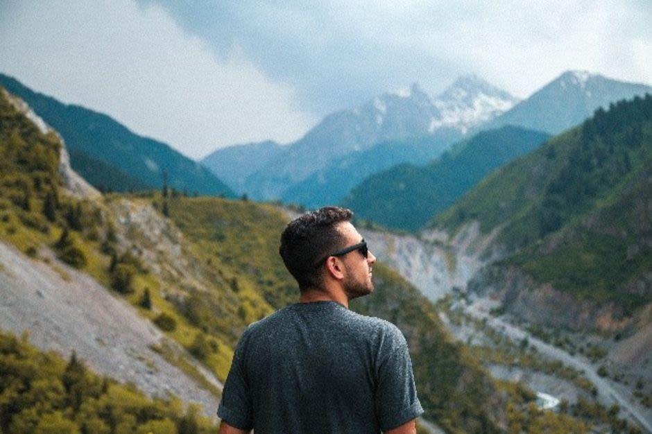 Mann mit Sonnenbrille schaut auf Berglandschaft
