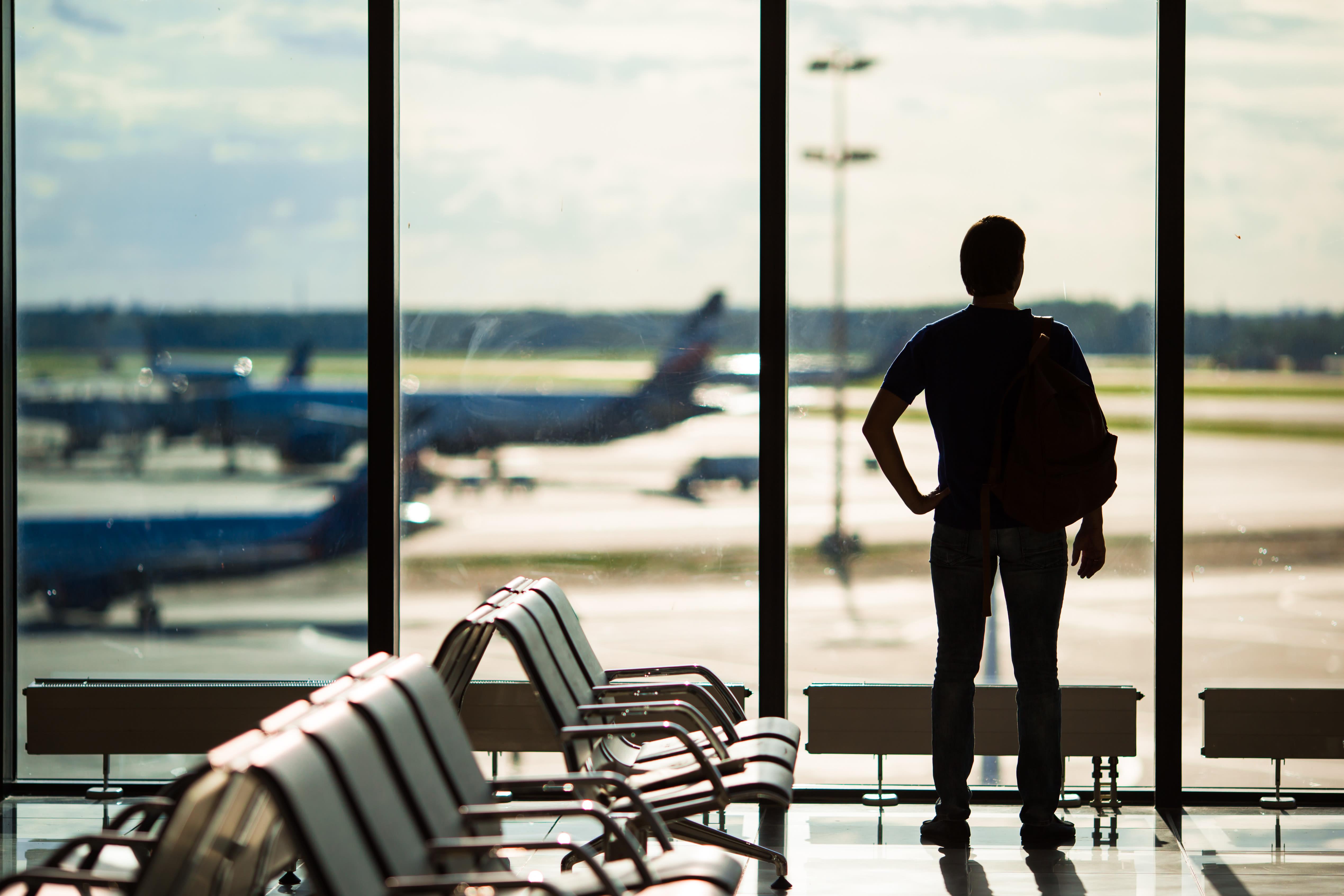 Man op een vliegveld, kijkend uit het raam naar vliegtuigen