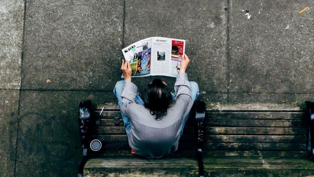Vista di un uomo dall'alto che legge un giornale seduto su una panchina