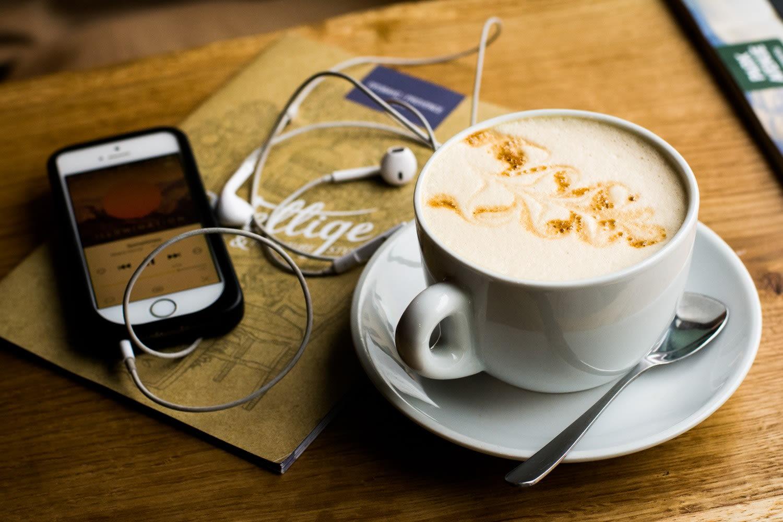 tazza di cappuccino con a fianco un iphone sintonizzato su un podcast