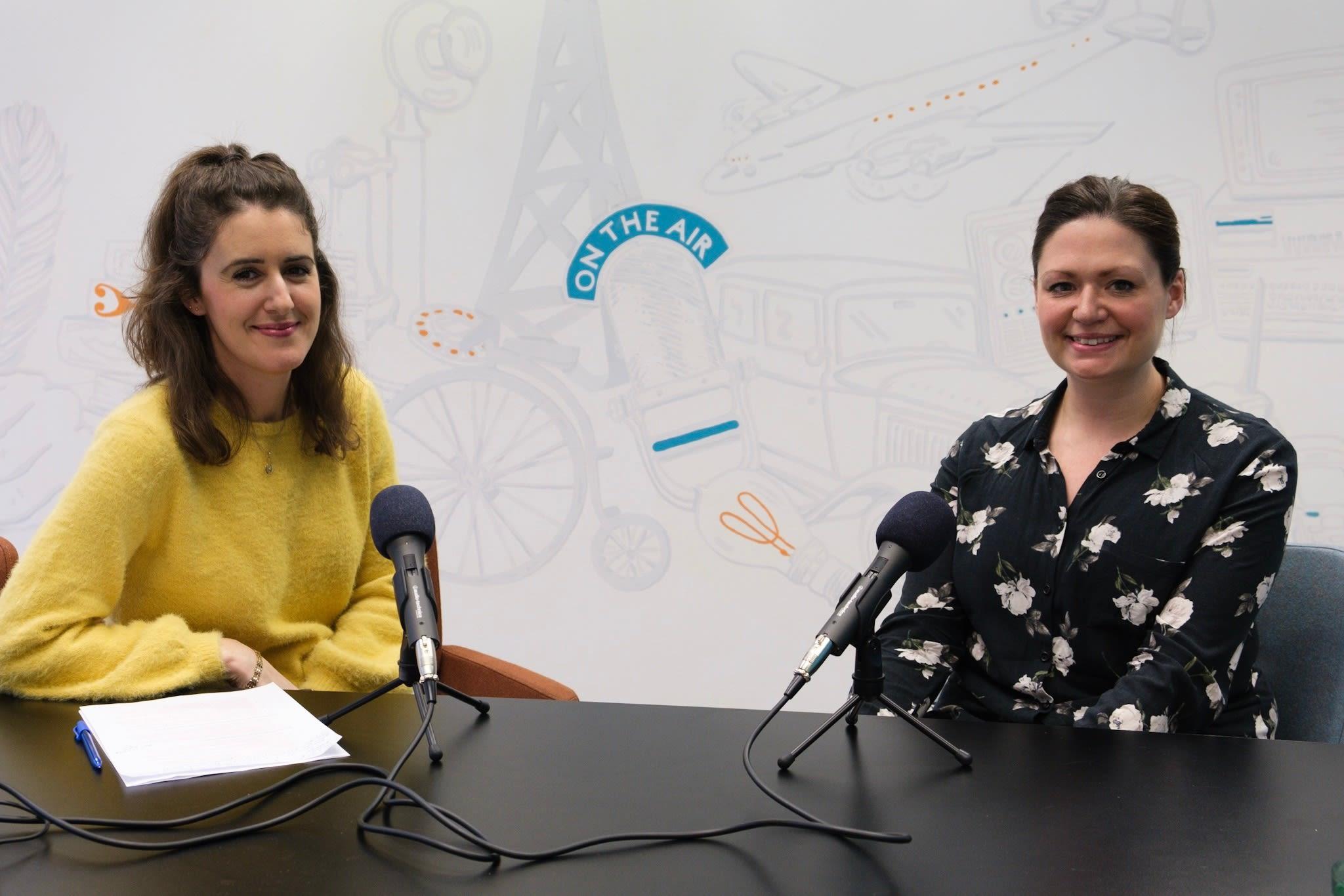 Zwei Frauen sitzen am Tisch mit Mikrofonen