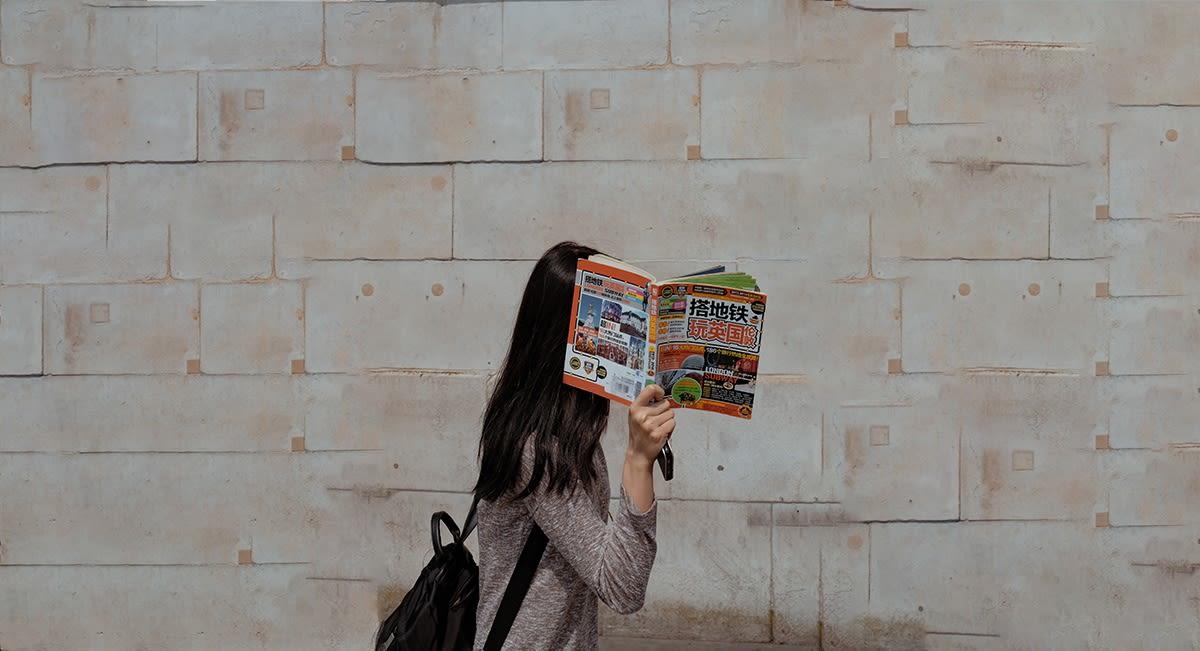 Frau hält Zeitung vors Gesicht