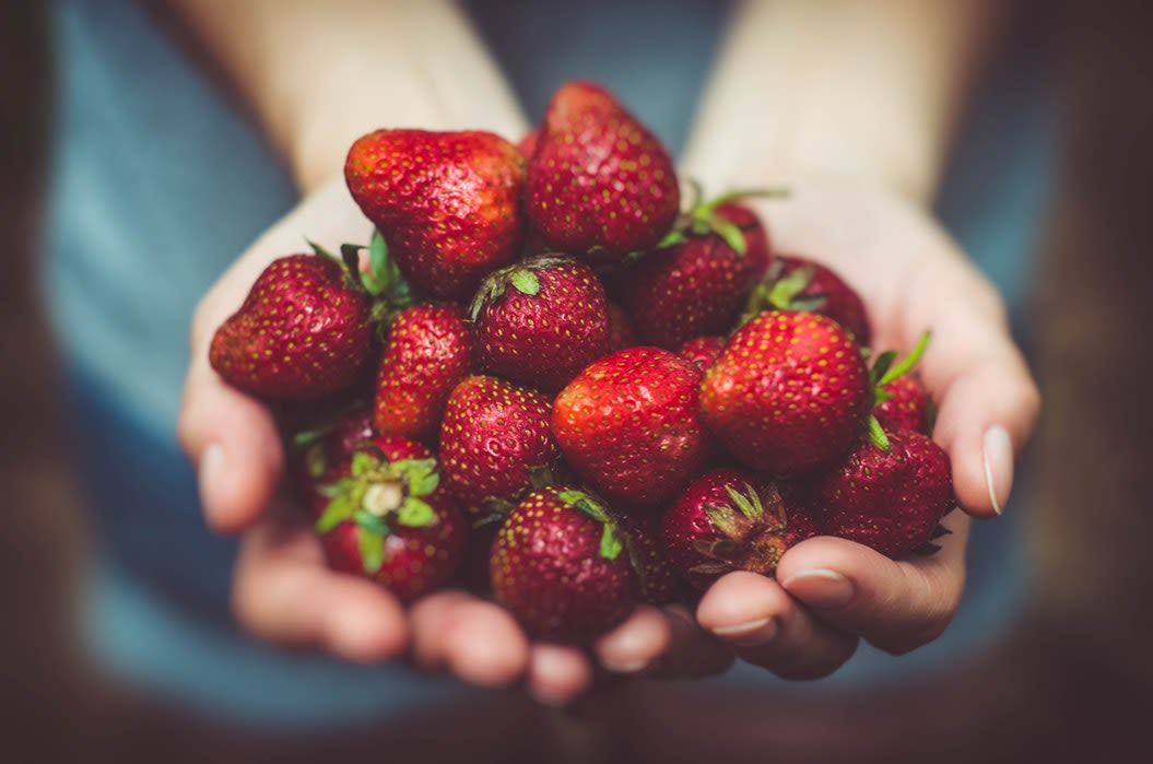 hand filled with strawberries