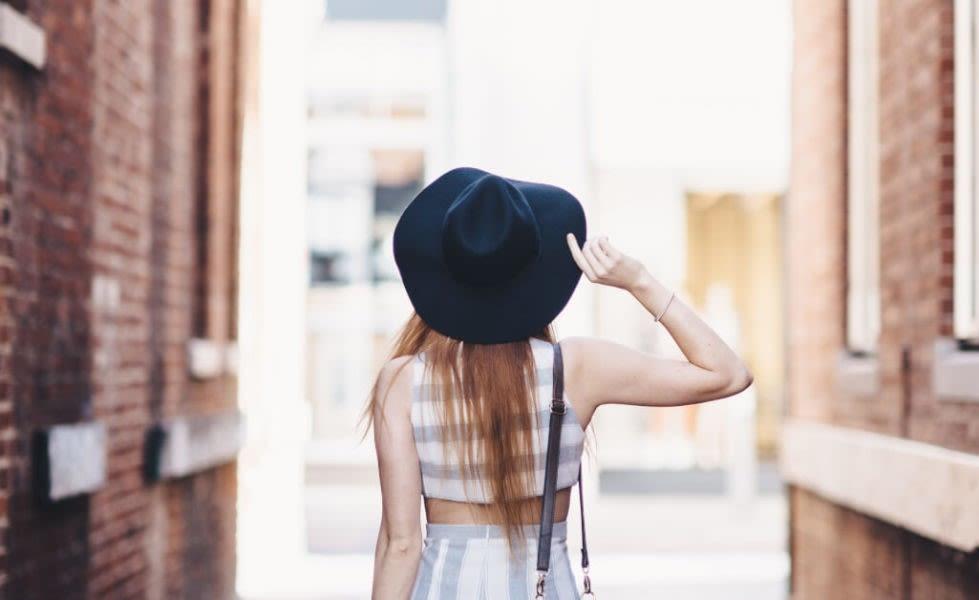 Frau mit schwarzem Hut von hinten