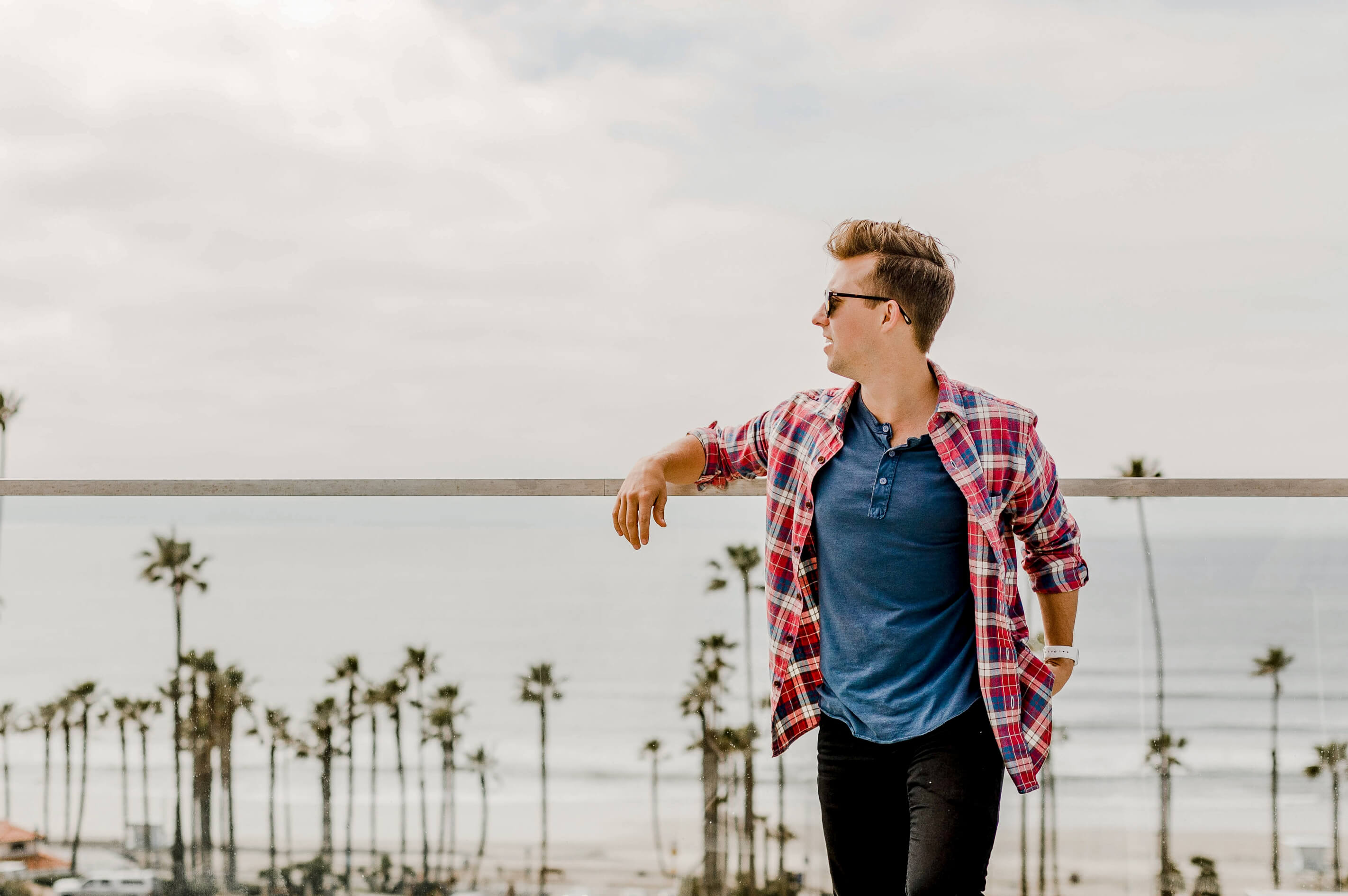 Junger Mann im roten Hemd vor Zaun