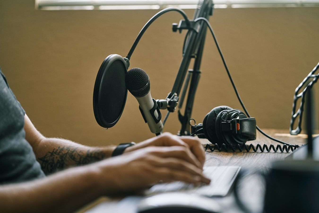 Man with microphone recording podcast in home studio