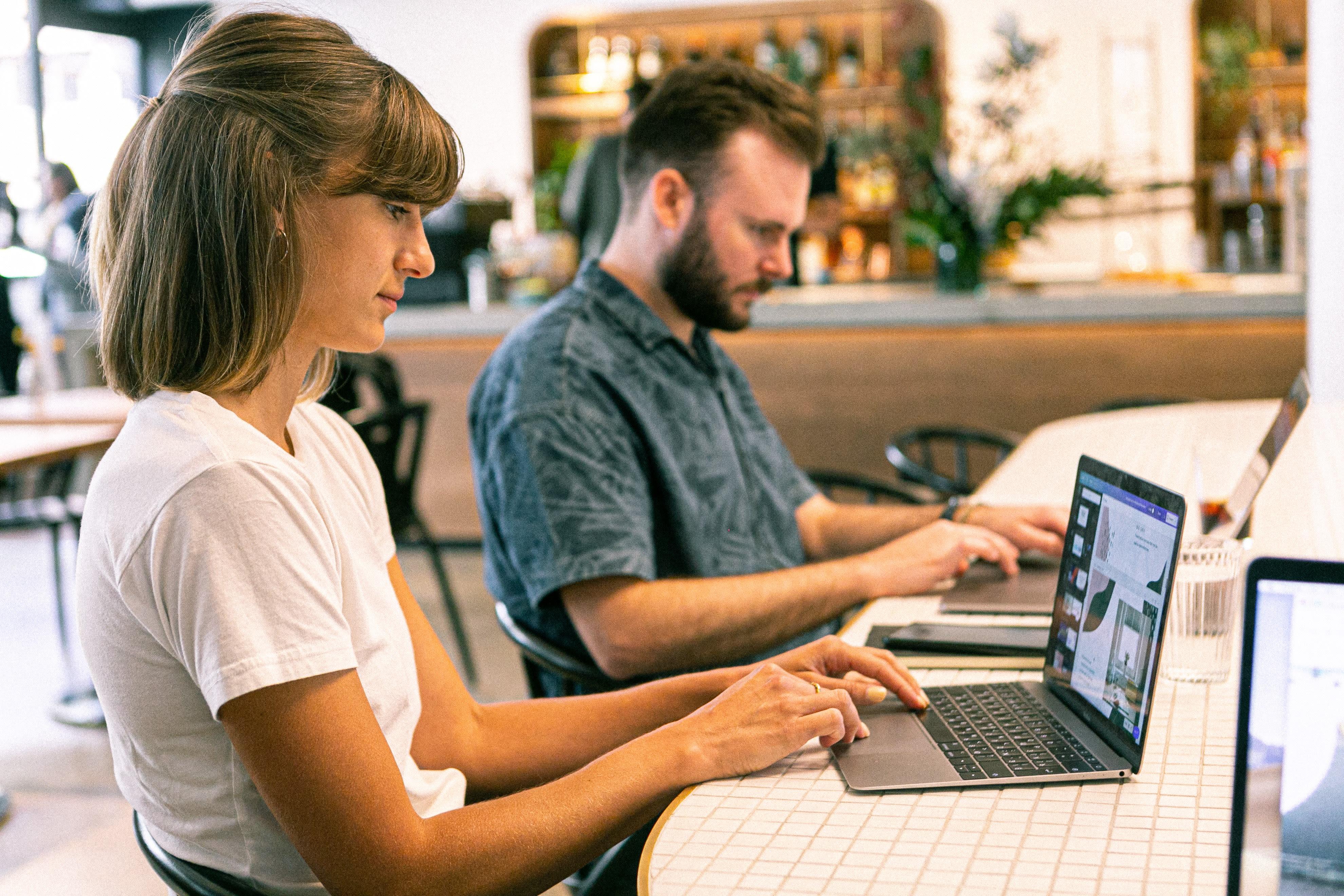 Frau und Mann sitzen mit Laptops an einem Tisch