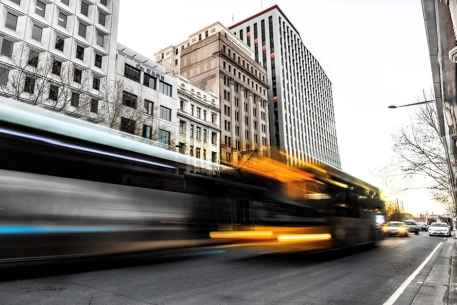An image of blurred traffic passing through a commercial area.