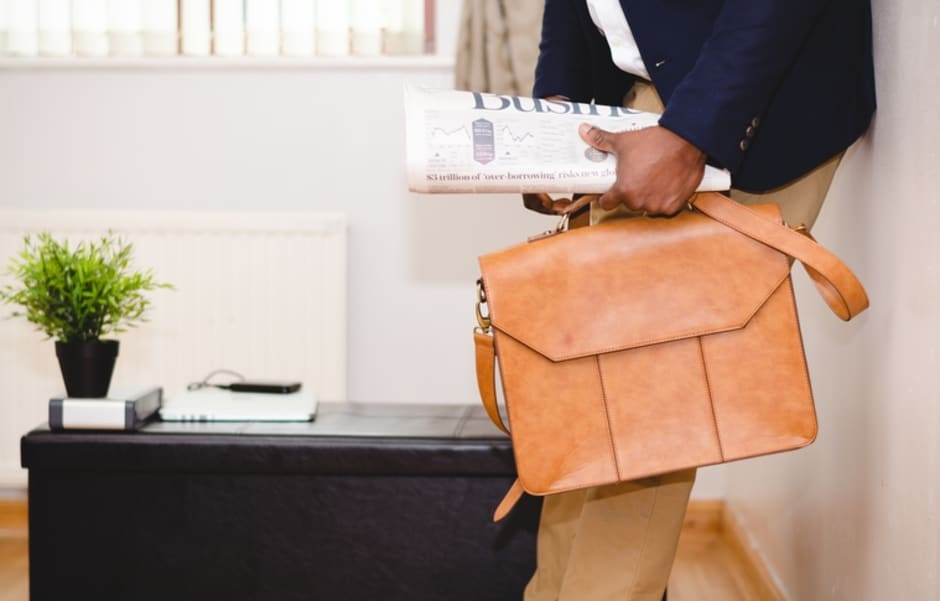 An image of a professional holding a briefcase and business trade press.