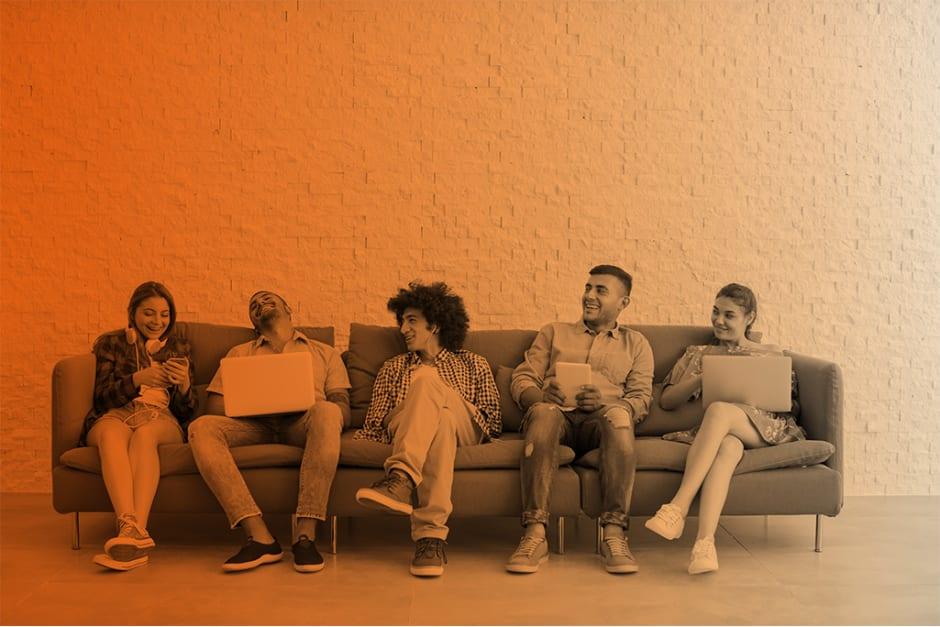 Fünf Leute sitzen lachend auf einer Couch