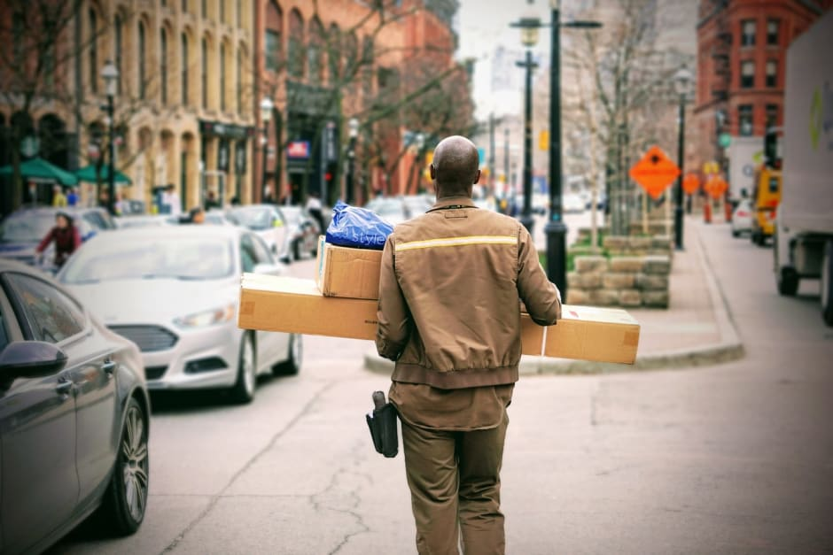 Man delivering boxes and parcels in city scape for online shopping retailer