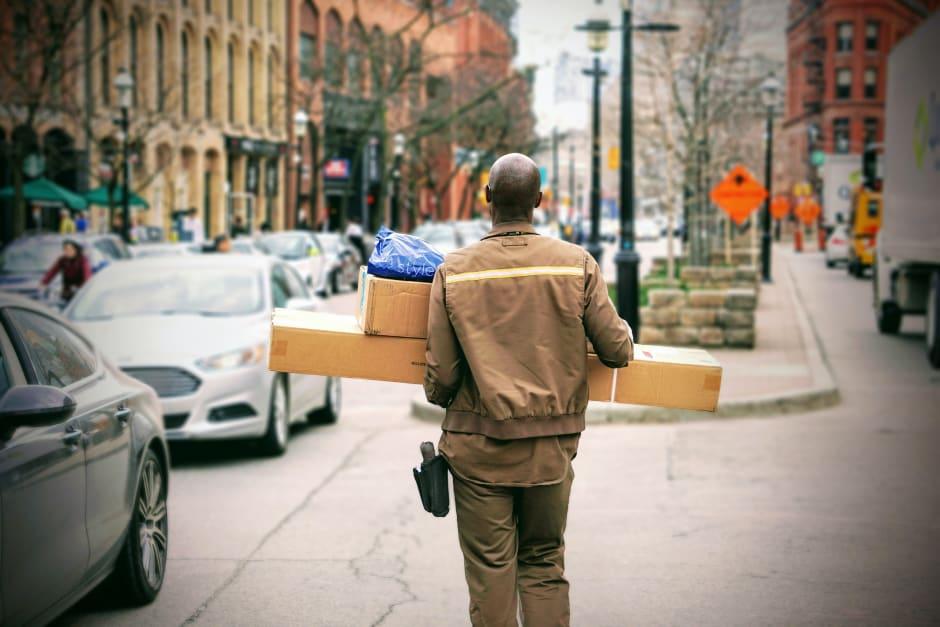 Mann in brauner Jacke trägt ein Paket