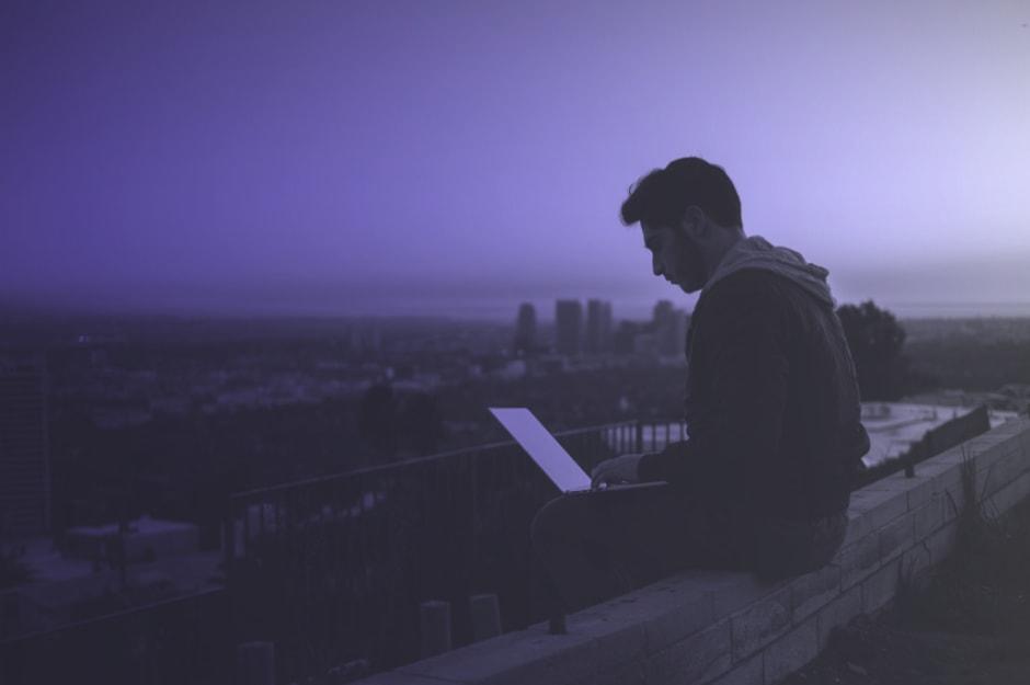 Mann sitzt mit Laptop auf einer Mauer