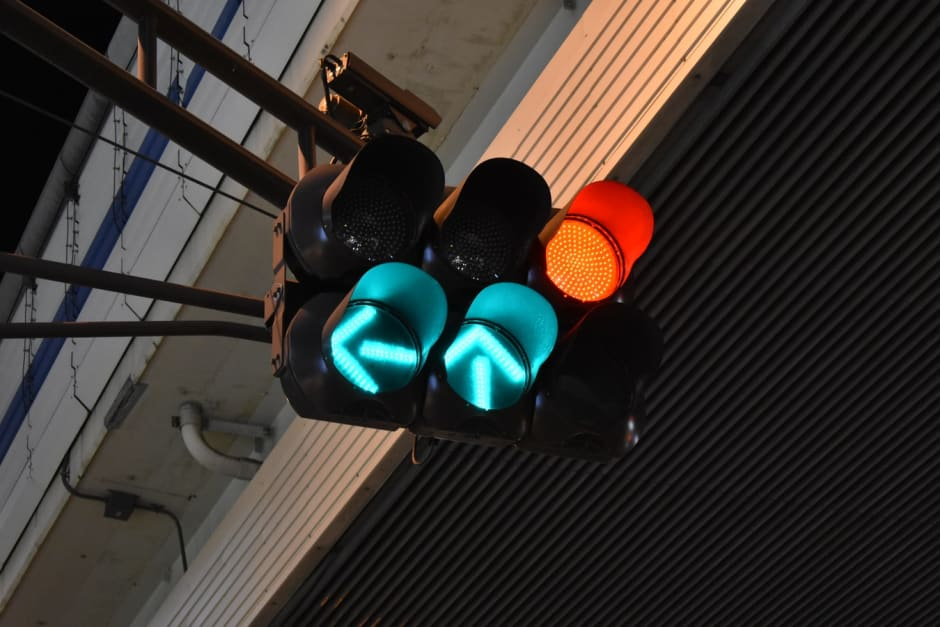 Green arrow and red traffic light in urban landscape