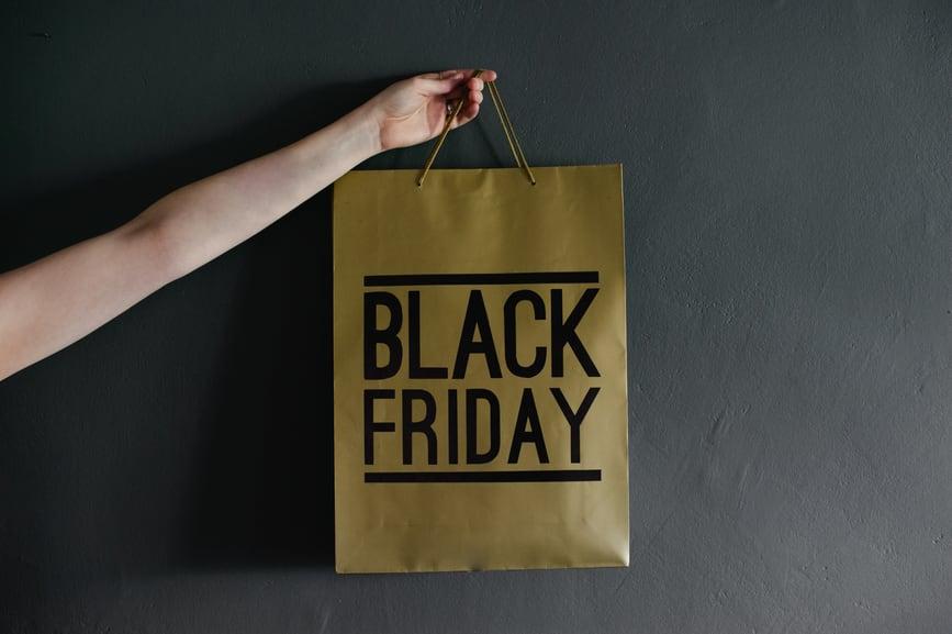 fotografia di un sacchetto in carta con sopra scritta Black Friday tenuto da una mano
