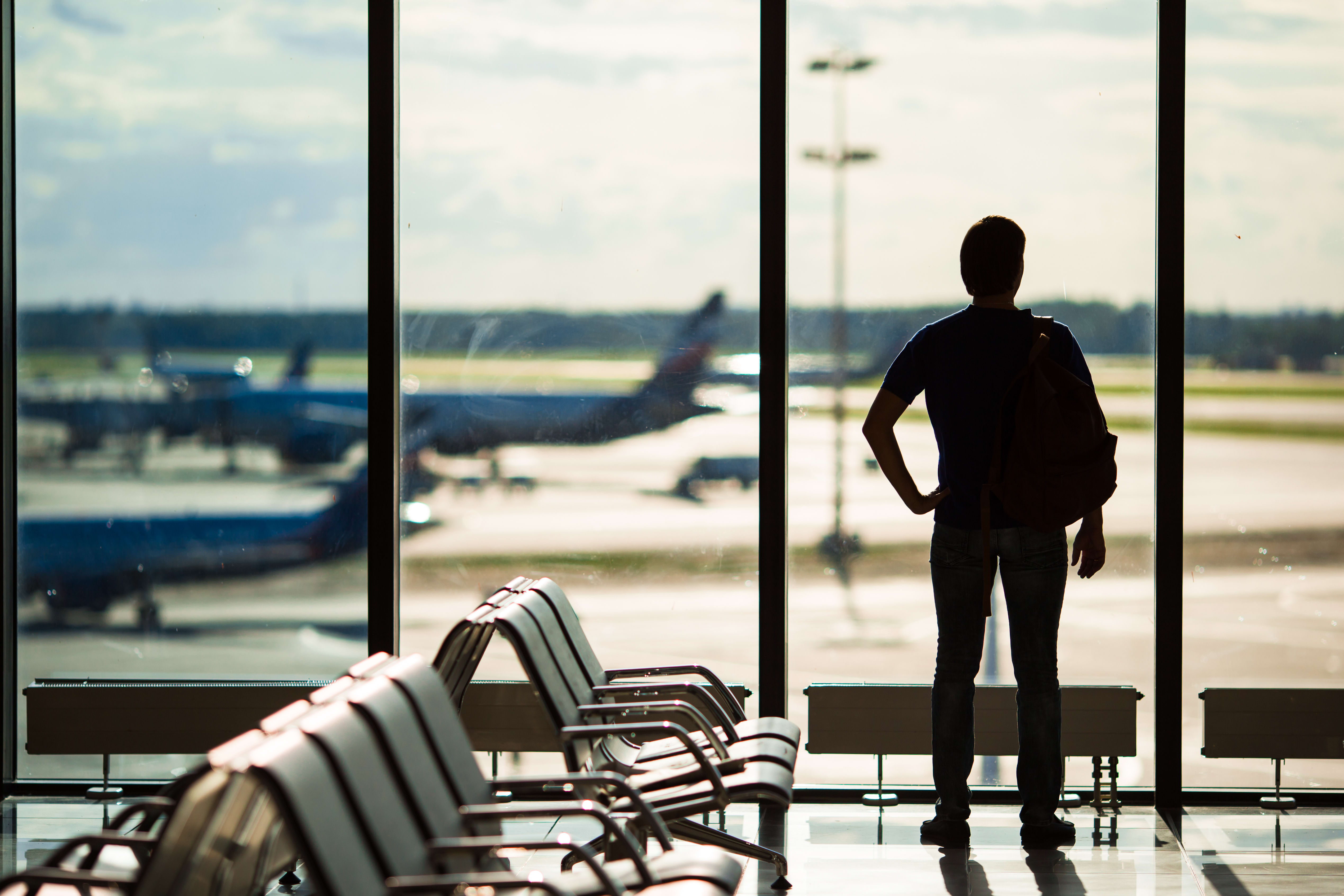 Man gazing out of an airport window at an aeroplane