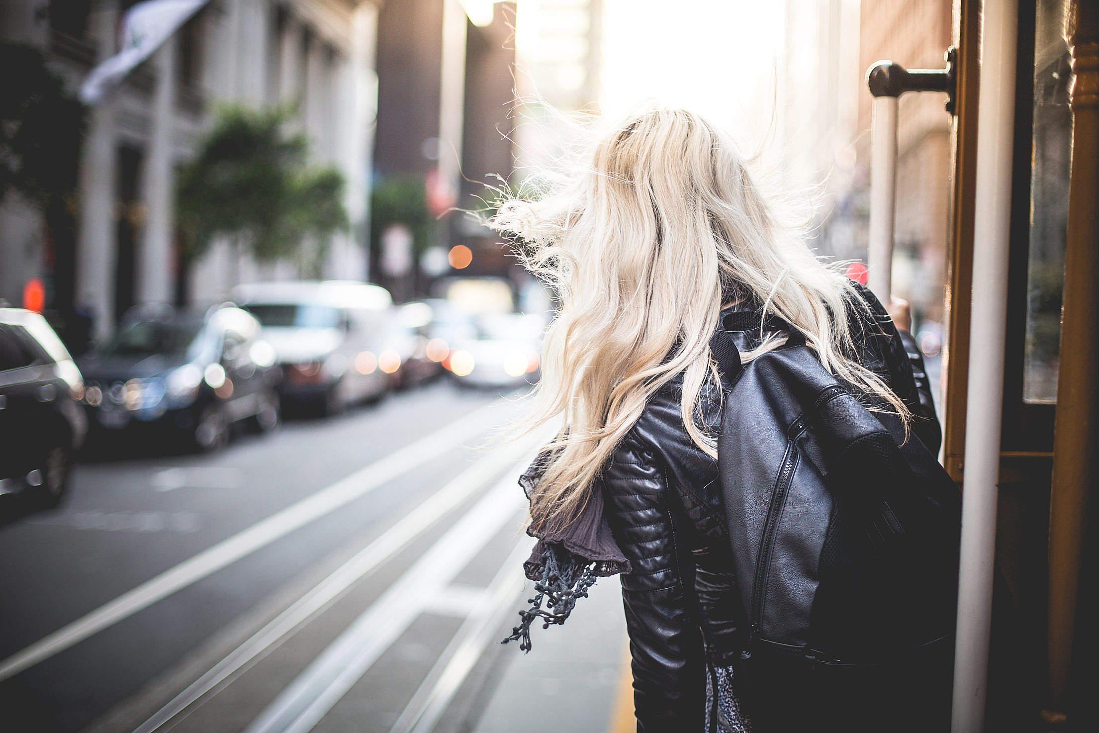 Ragazza bionda vista di spalle che scende da un tram