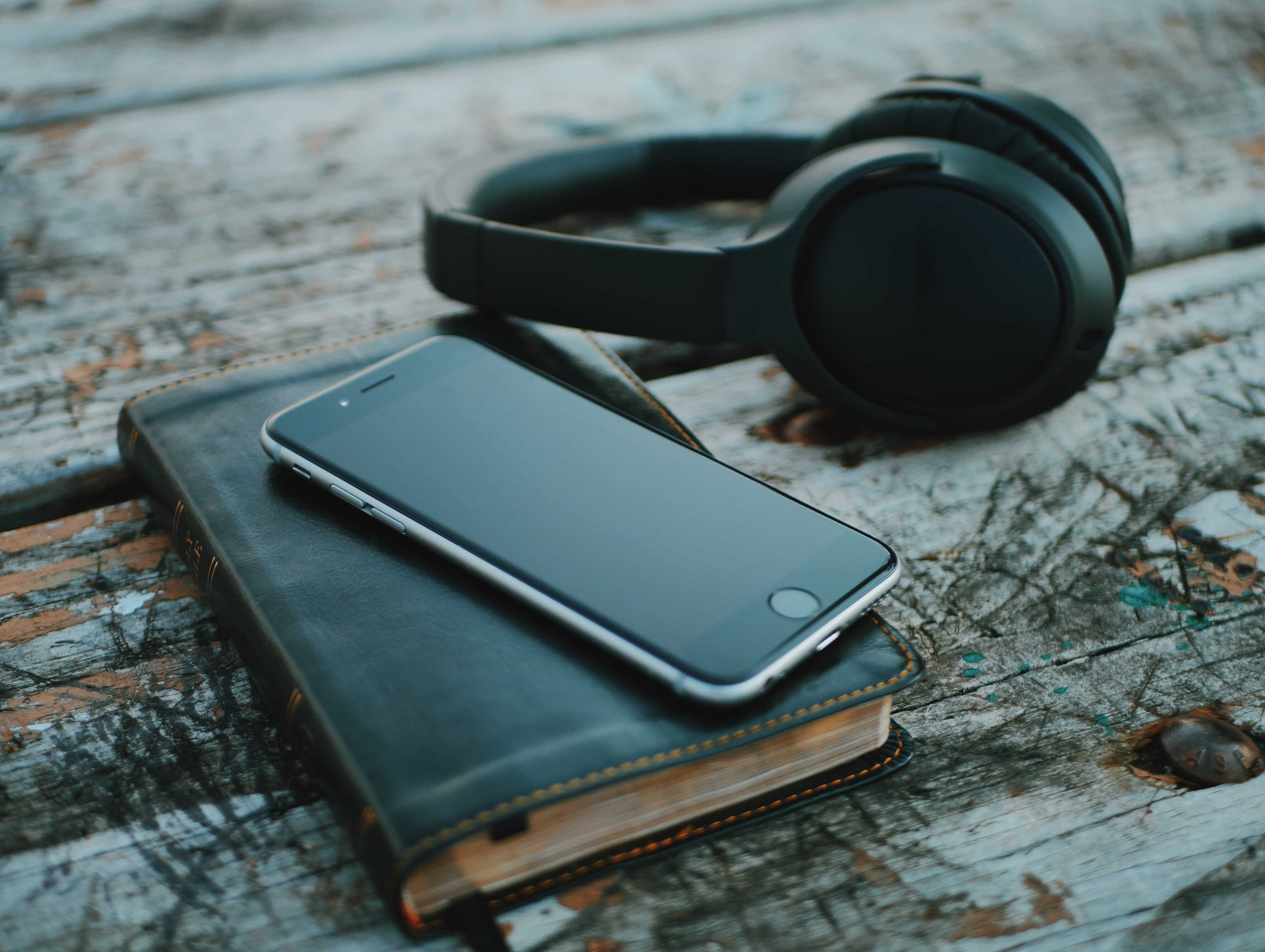 cellulare appoggiato sopra un'agenda e cuffie per ascoltare
