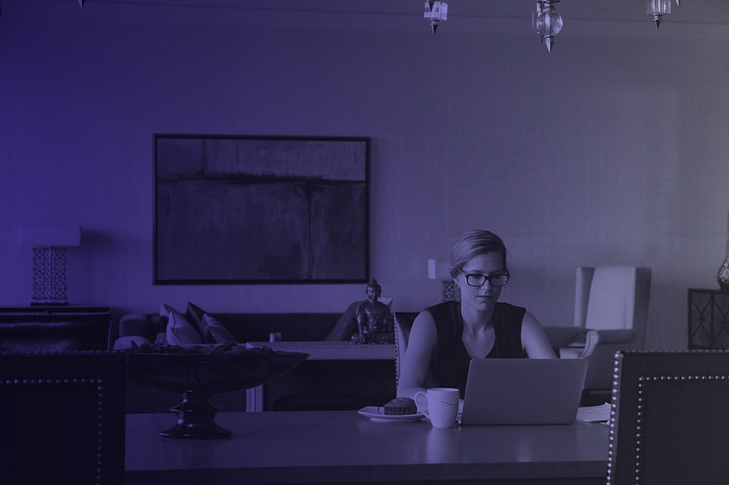 Blonde Frau sitzt mit Laptop am Tisch