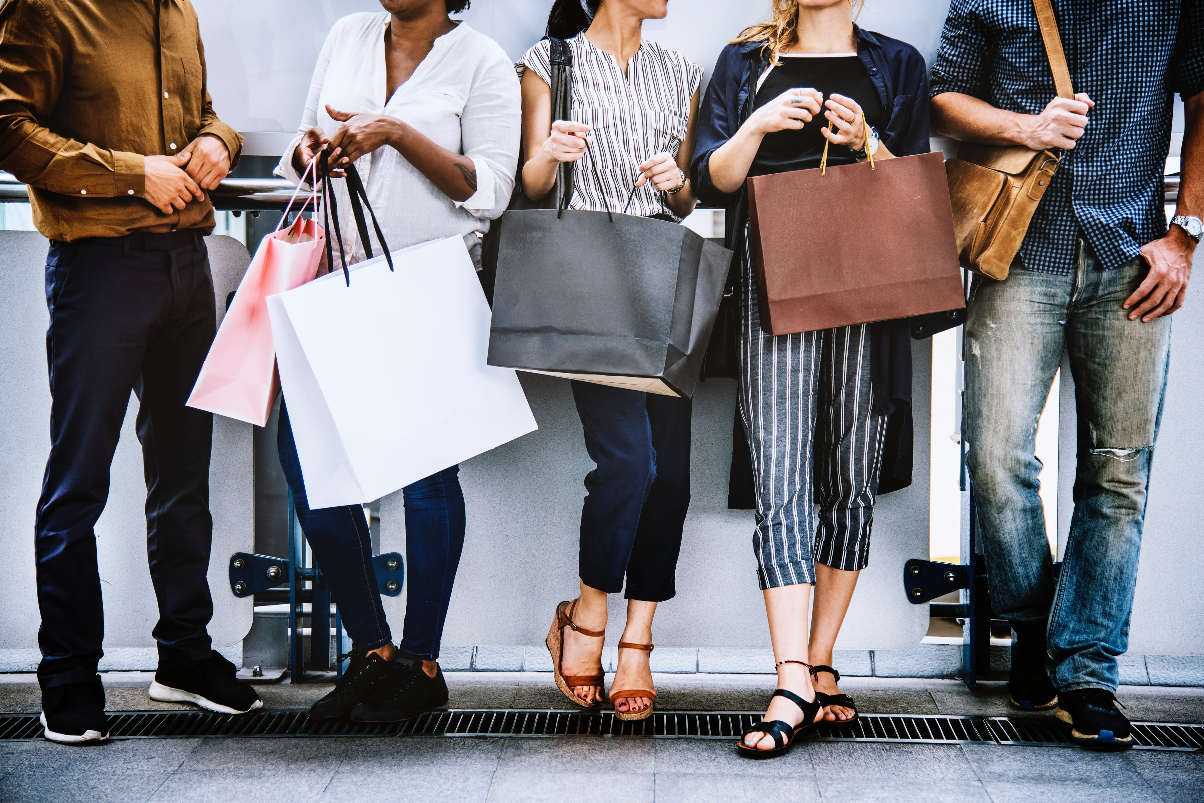 Shoppers standing around with shopping bags