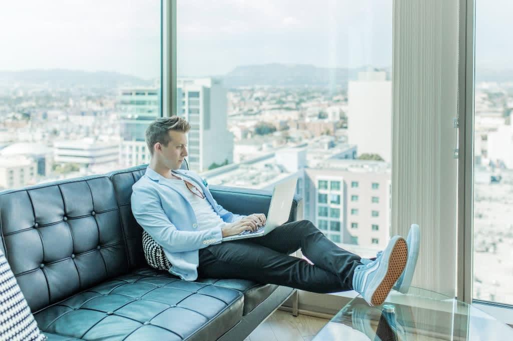 Mann mit Laptop sitzt auf schwarzem Ledersofa