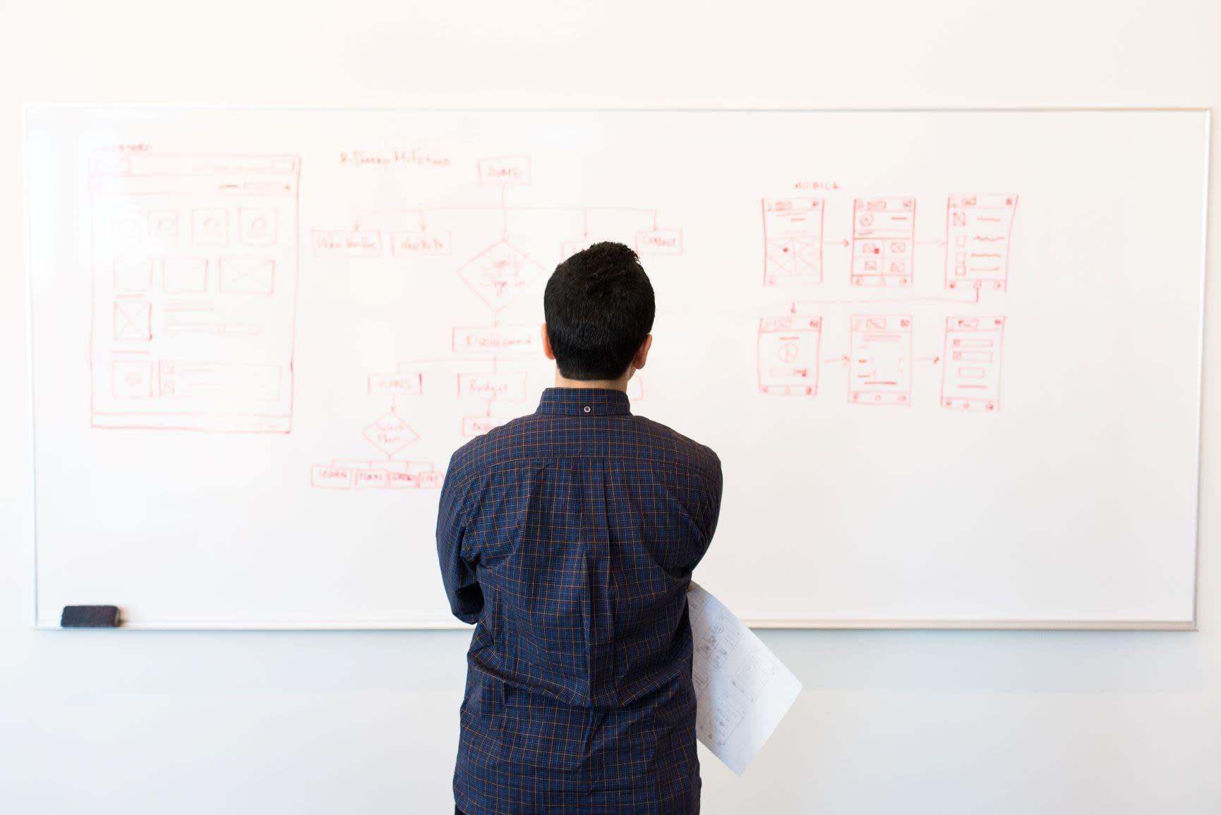 Mann steht vor Whiteboard mit roter Schrift