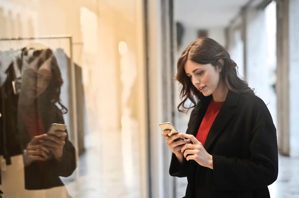Ragazza con il telefono in mano davanti alla vetrina di un negozio
