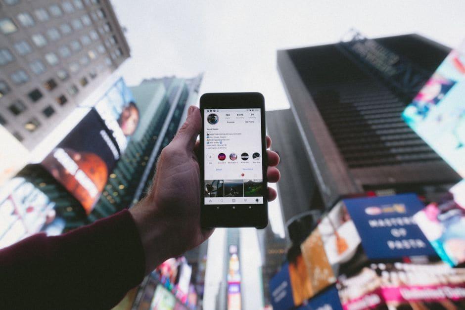 Handy in der Hand in einer Großstadt