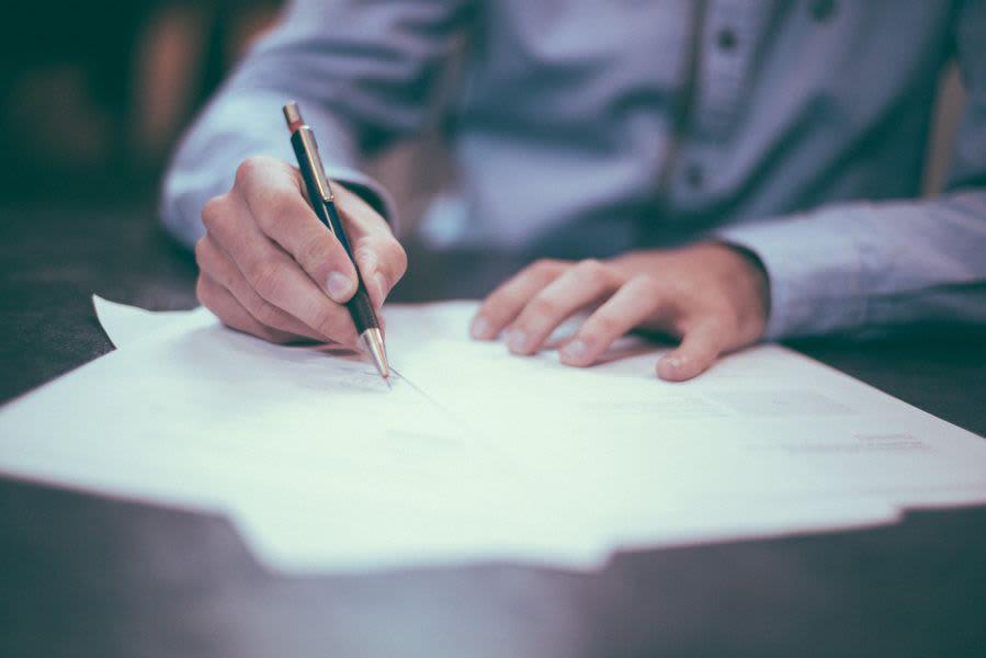 Mann unterschreibt einen Vertrag