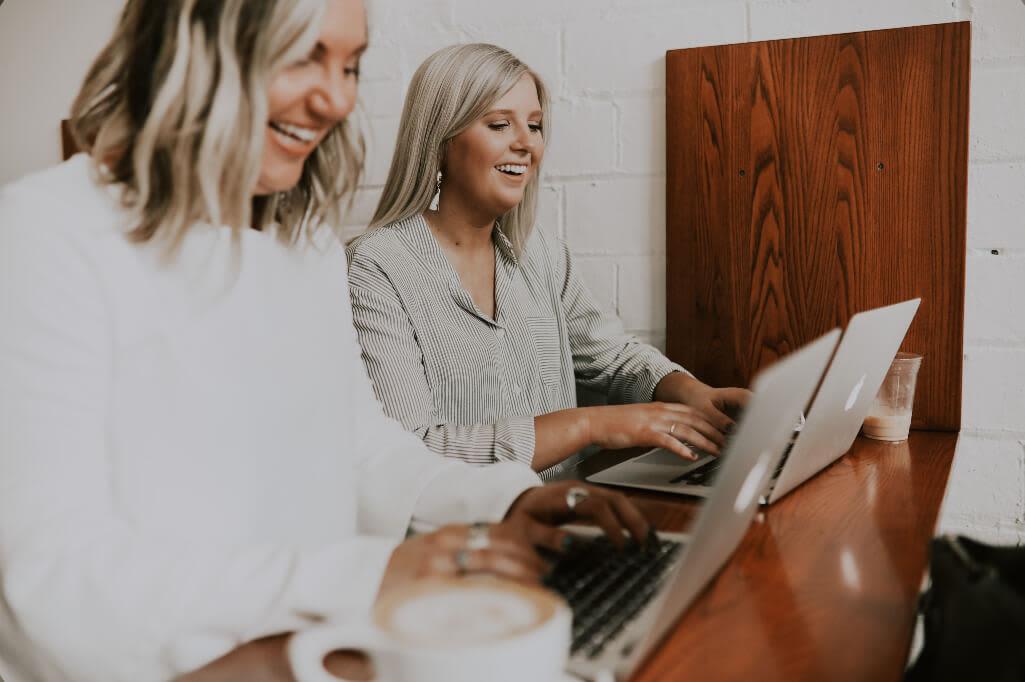 zwei blonde Frauen arbeiten lachend an Laptops