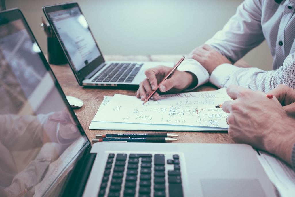 zwei Laptop stehen auf einem Tisch, Hände arbeiten dran