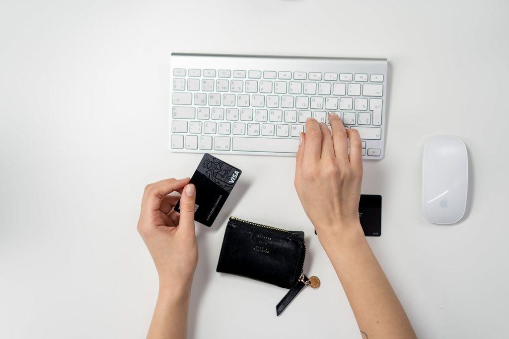 una mano sulla tastiera e una mano che regge la carta di credito