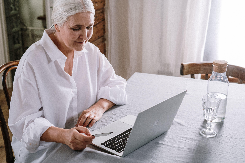 ältere Dame sitzt am Laptop und hält Kreditkarte in der Hand