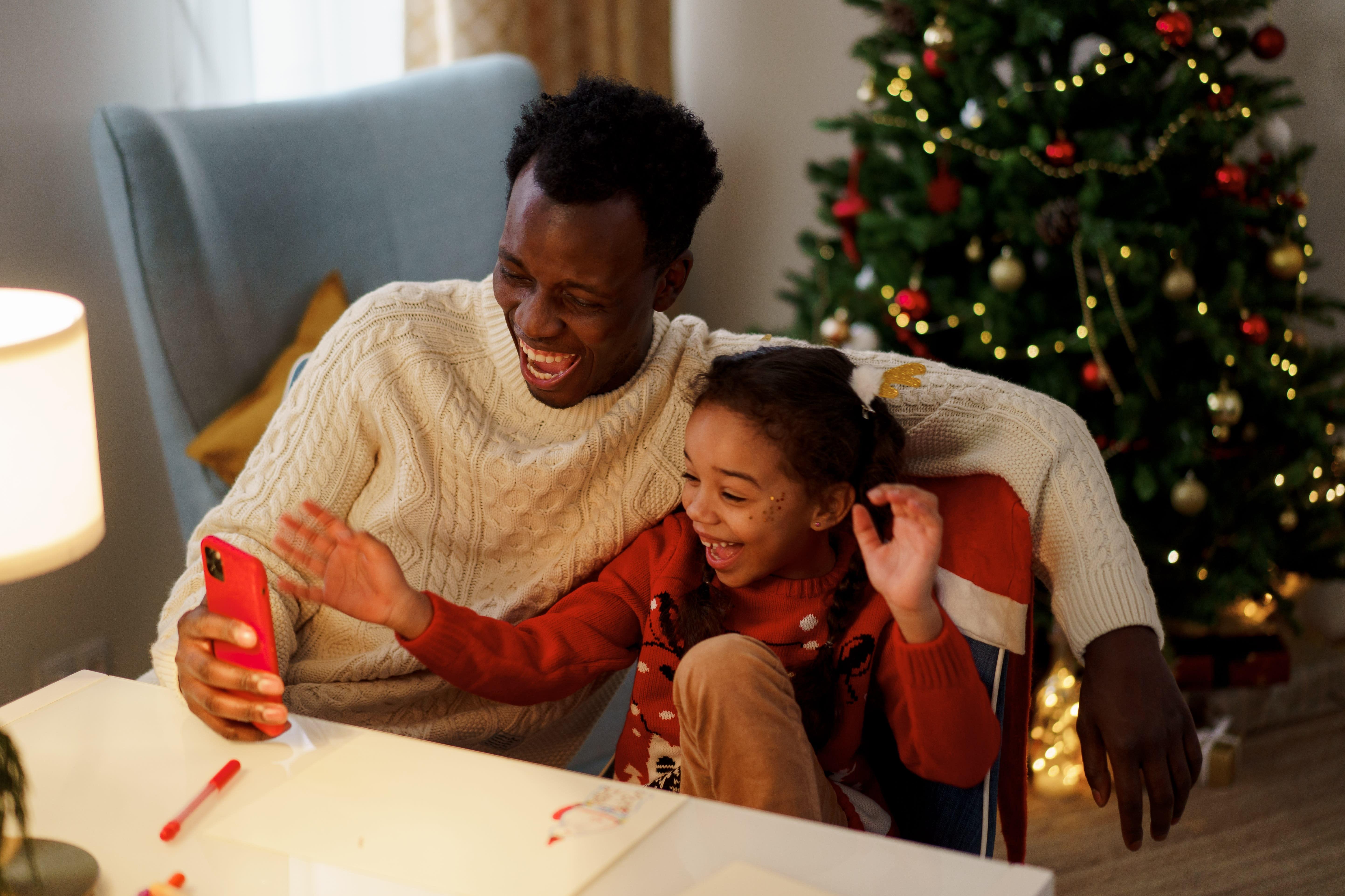 Vater und Tochter in Weihnachtspullovern schauen lachend aufs Smartphone