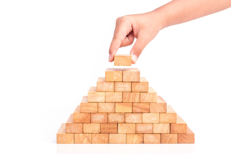 An image of a final wooden building block being placed at the top of a pre-built pyramid shape alluding to building an affiliate marketing strategy.